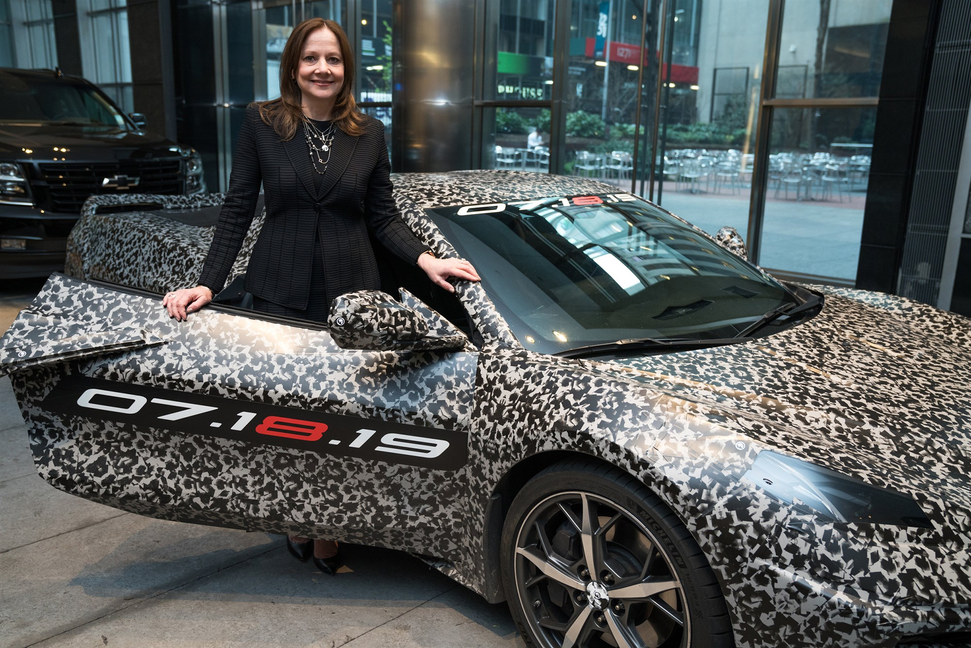 CEO Mary Barra stands with a camouflaged next generation Chevrolet Corvette